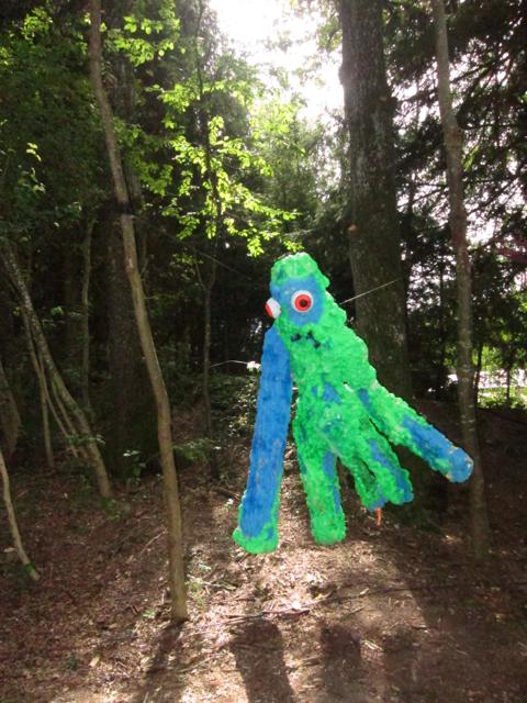 Ein grüner Waldgeist in den Bauemen haengend